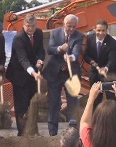 "Three men with a shovel. While Mayor Paul Dyster (left) may not make a good Santa Claus for the taxpayers of Niagara Falls, he has been a good Santa to millionaire developers like Mark Hamister (center).  Above, Hamister gets help from Mayor Dyster and Gov. Andrew Cuomo (right) in breaking ground for a small hotel with a lot of subsidies, some 300 feet from the entrance to the Niagara Falls State Park.  The Reporter believes the deal involved initially a rigged selection scheme and later a fraudulently, provably, inflated price tag for the smallish, low amenities hotel to be built on one of the most important undeveloped sites in Niagara Falls - in order to secure millions more in taxpayer subsidies for Hamister.   There is a chance that Dyster and Cuomo were secretly complicit in arranging the financing scheme. As Franklin said, ""Three can keep a secret if two of them are dead."" Let's see how this shakes out."